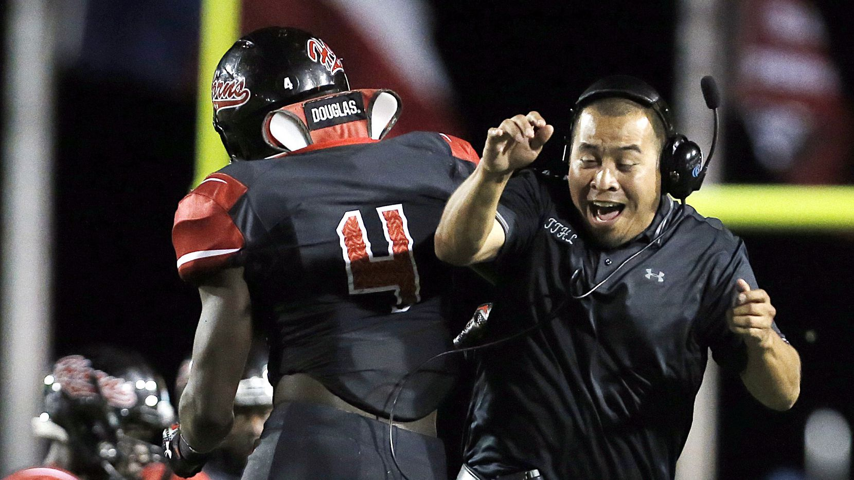 Cedar Hill defensive line coach Francisco Sandoval, right, celebrates with senior linebacker Xavier Hall (4) a fourth down stop against Skyline during the first half of a high school football game at Cedar Hill High School, Friday, September 11, 2015.