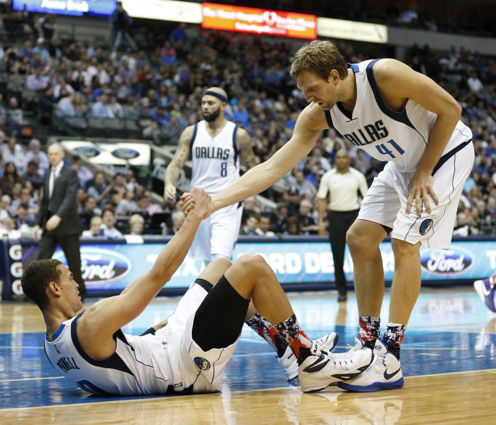 Dallas Mavericks forward Dirk Nowitzki (41) helps up Dallas Mavericks forward Dwight Powell (7) against the Charlotte Hornets at the American Airlines Center inthe second half  Dallas, Thursday, November 5, 2105.  Dallas lost the game 108-94. (Nathan Hunsinger The Dallas Morning News)