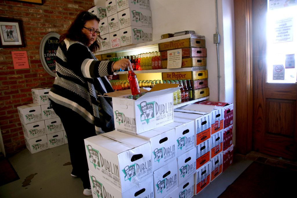 Kathy Wells of Miles loads up a case of various flavors of sodas for her grandson's birthday at Doc's Soda Shop in Dublin. Dublin Bottle Works has about a dozen flavors of soft drinks and carries a few other brands from out-of-state bottlers. (Guy Reynolds/The Dallas Morning News)
