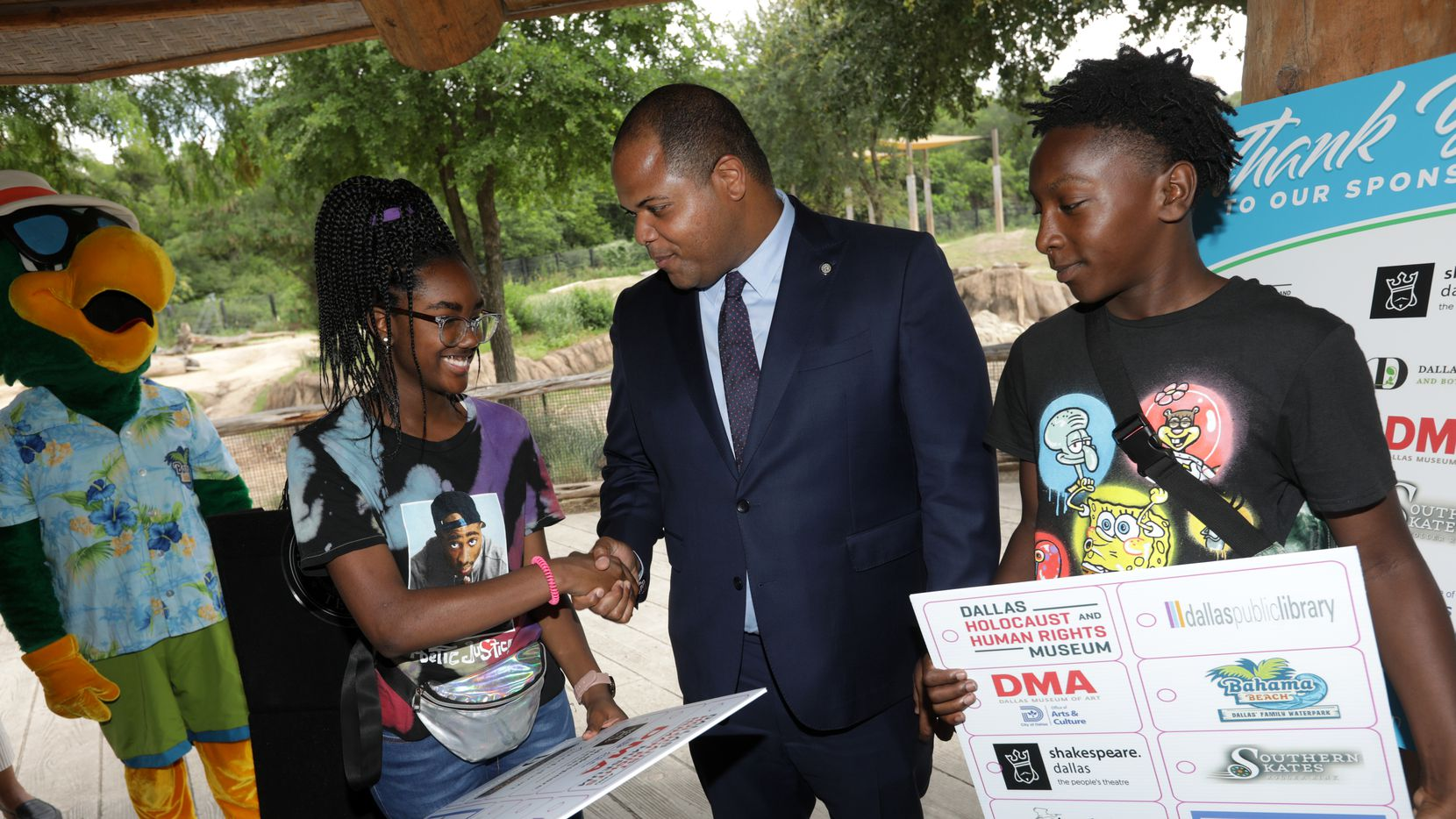 Mayor Eric Johnson, center, gives 14-year-old Kamryn Jones, left, and 13-year-old Isaiah Wilson a Youth All-Access Pass during a press conference at the Dallas Zoo in Dallas, TX, on Jun. 29, 2021.  (Jason Janik/Special Contributor)