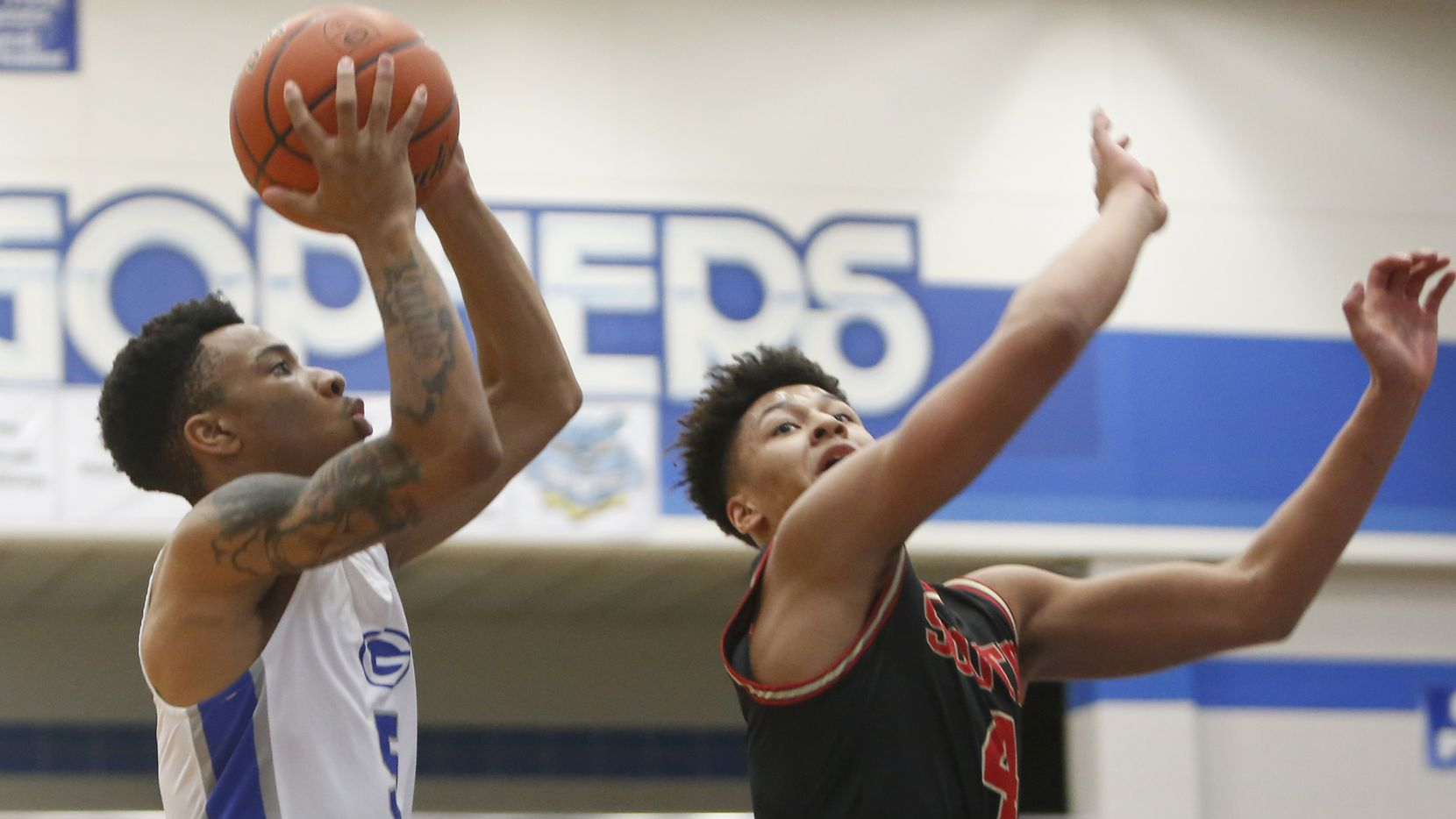 Grand Prairie's Donovan Newton (left) drives to the basket as he is defended by South Grand Prairie's Khaden Bennett during Grand Prairie's 72-68 win Saturday at Grand Prairie High School.  (Steve Hamm/ Special Contributor)