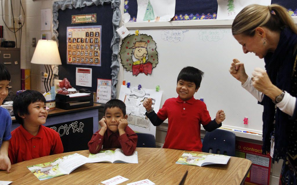 """Burmese refugees, many of whom never attended any school before, get extra help at Wallace Elementary School in Richardson ISD in 2011. Diane Royer worked with her second-grade students and pantomimed the word """"furious"""" for some of the children during an English vocabulary lesson. From left: Bawi Cung, 9, Nay Kaw Htoo, 8, Ta Ree, 8, Su Reh, 9, and Ms. Royer.  (File Photo/Staff)"""