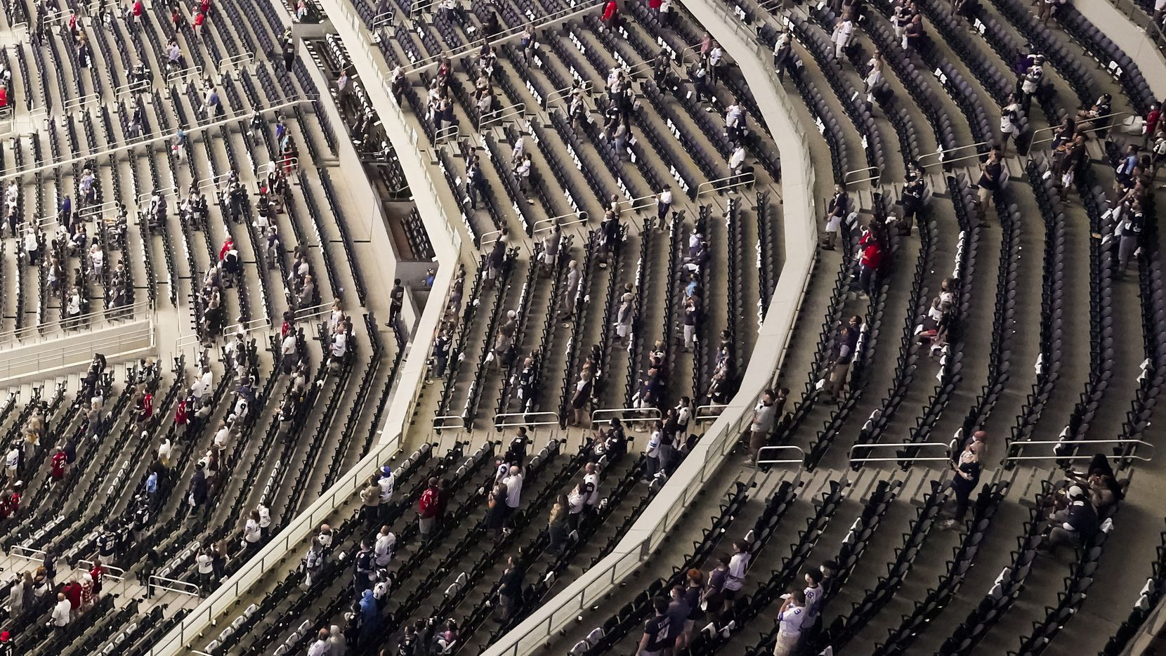 "A socially distanced crowd, separated into what team officials described as ""pods,"" stands for the national anthem before a game between the Cowboys and Falcons at AT&T Stadium on Sunday, Sept. 20, 2020, in Arlington."
