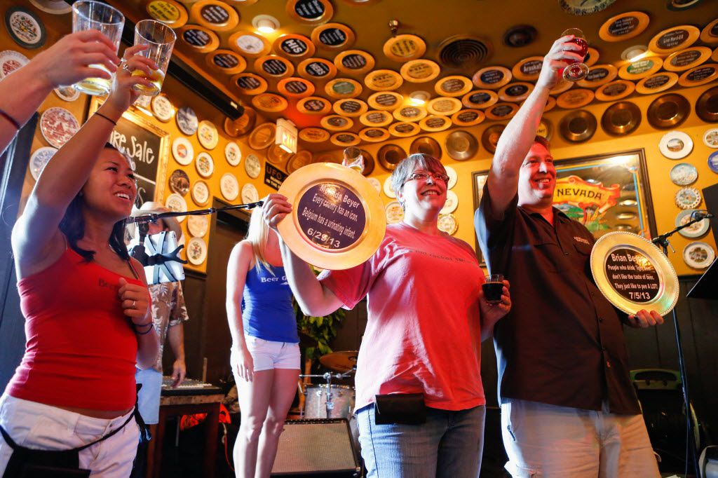 Waitstaff of The Flying Saucer in Addison, Texas celebrate Melinda Beyer (center) and Brian Beyer (right) at the BeerBQ event on Sunday, July 21, 2013 for having drunk the circut of 200 beers five and eleven times respectively.