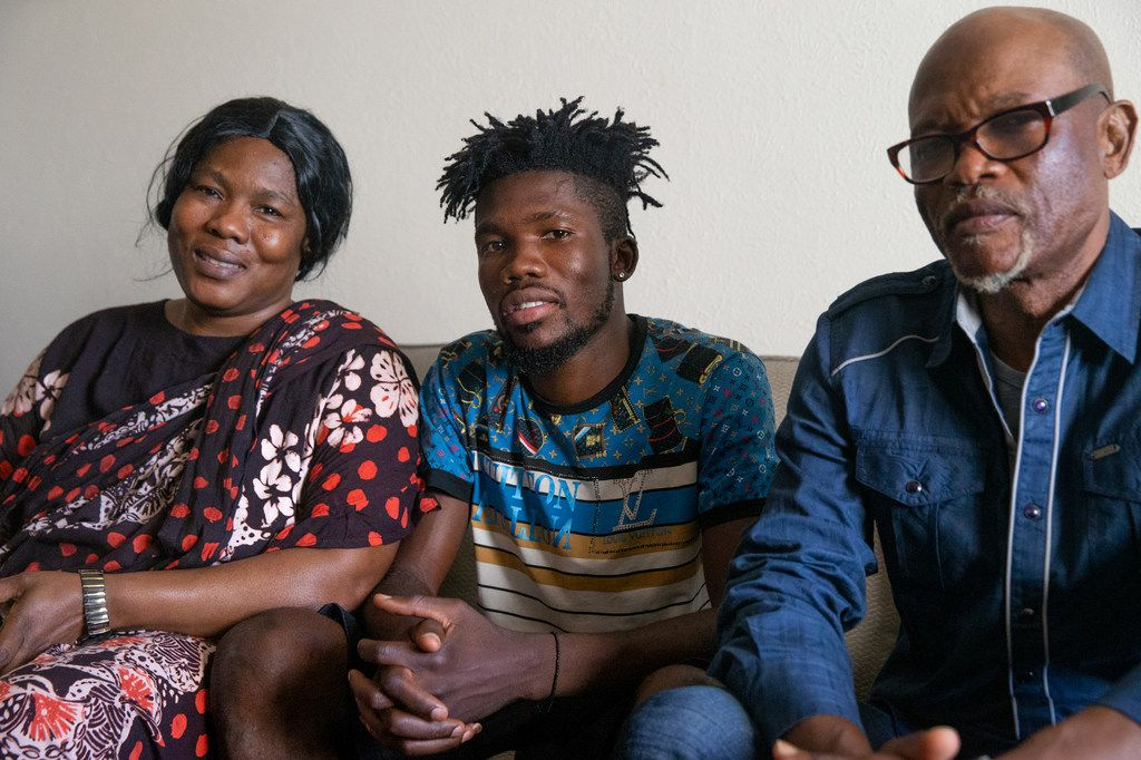 Isaac Alingabo (center), a refugee from the Democratic Republic of the Congo, poses for a portrait with his parents, Elizabeth and Jean Rene Alingabo,  in his Dallas apartment.