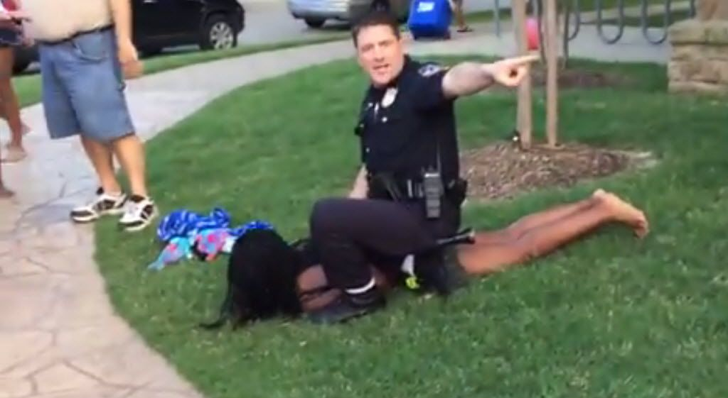 McKinney police Officer Eric Casebolt warns others away as he kneels on a female teen as he handcuffs her after throwing her to the ground at a pool party on June 5, 2015.