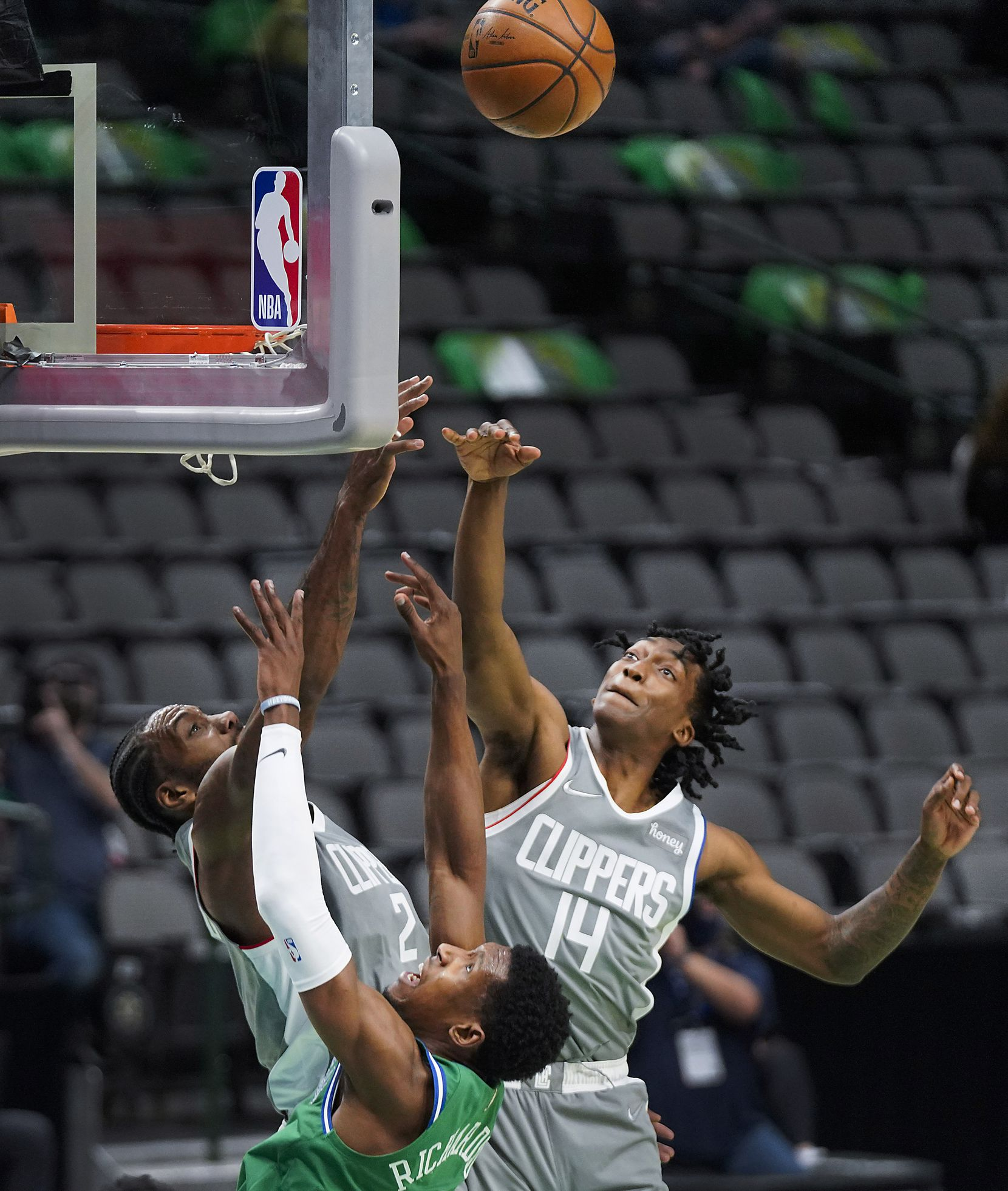 Dallas Mavericks guard Josh Richardson (0) puts up a shot a LA Clippers forward Kawhi Leonard (2) and guard Terance Mann (14) defend during the during the first half of an NBA basketball game at American Airlines Center on Wednesday, March 17, 2021, in Dallas.