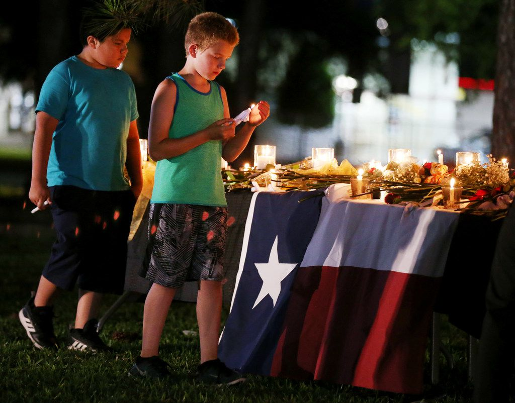 Children carry candles following a vigil along Avenue M and Highway 6 following a shooting at Santa Fe High School on May 18.