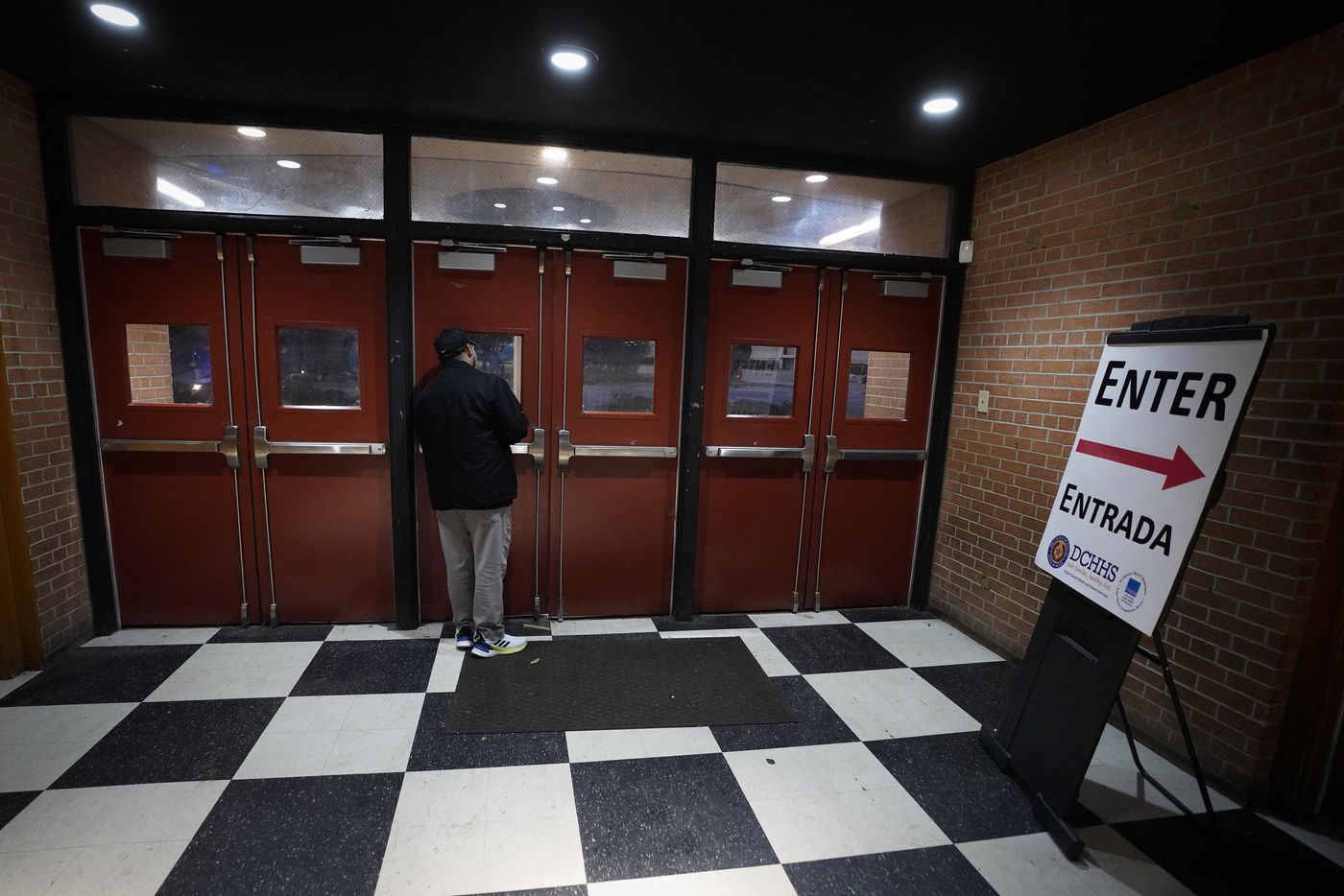 An employee of the Dallas County Department of Health and Human Services waits for people to open the door to receive the COVID-19 vaccine at Fair Park in Dallas on Monday, January 11, 2021. Dallas County launched its first