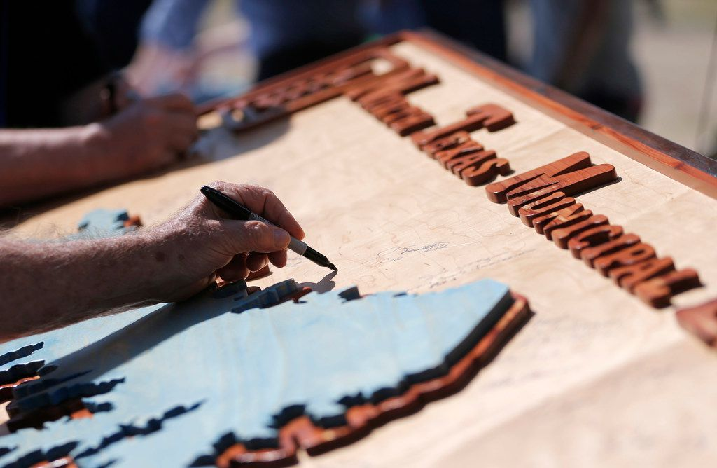 Joe Joplin of North Texas Municipal Water District signs a wooden board with a carved out replica of the future North Texas Municipal Lake during the ground breaking ceremony in unincorporated Fannin County on  May 25.