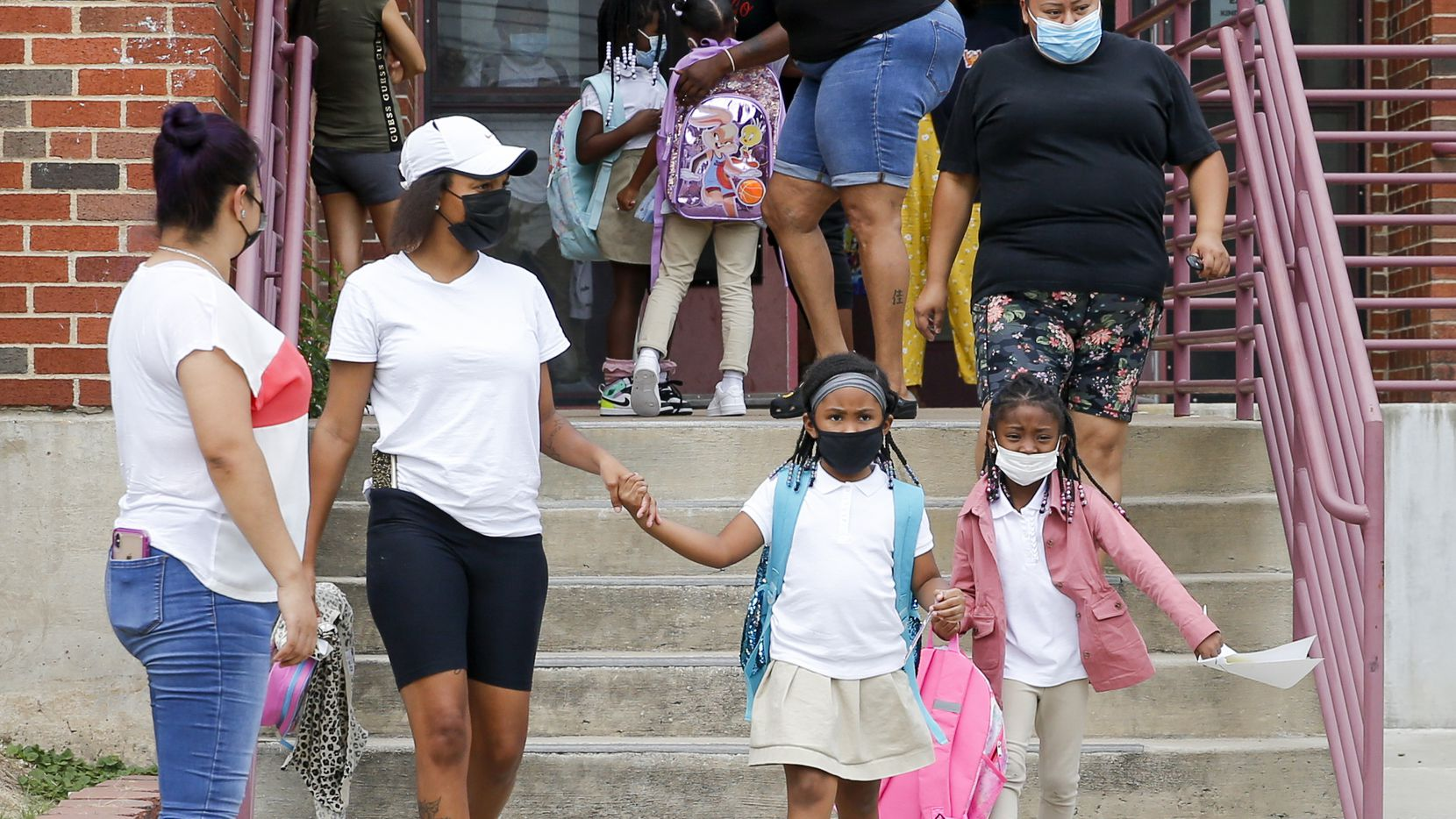 Parents pick up their children after school at Paul L. Dunbar Learning Center on Wednesday, Sept. 8, 2021, in Dallas. (Elias Valverde II/The Dallas Morning News)