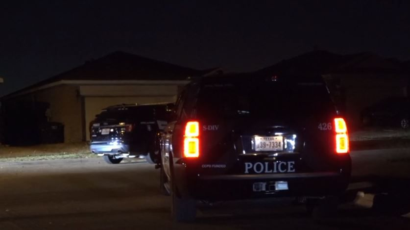 Police vehicles sit outside a home in Fort Worth near where shooting broke out between a group of teenagers Tuesday night. Three juveniles were injured.