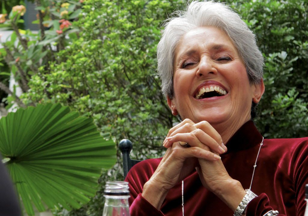 In this April 6, 2013 photo, Joan Baez laughs while speaking to former staff at the Metropole Hanoi in Hanoi, Vietnam.  The folk singer and social activist visited Vietnam recently for the first time since she came to the country in December 1972 as part of an American peace delegation.