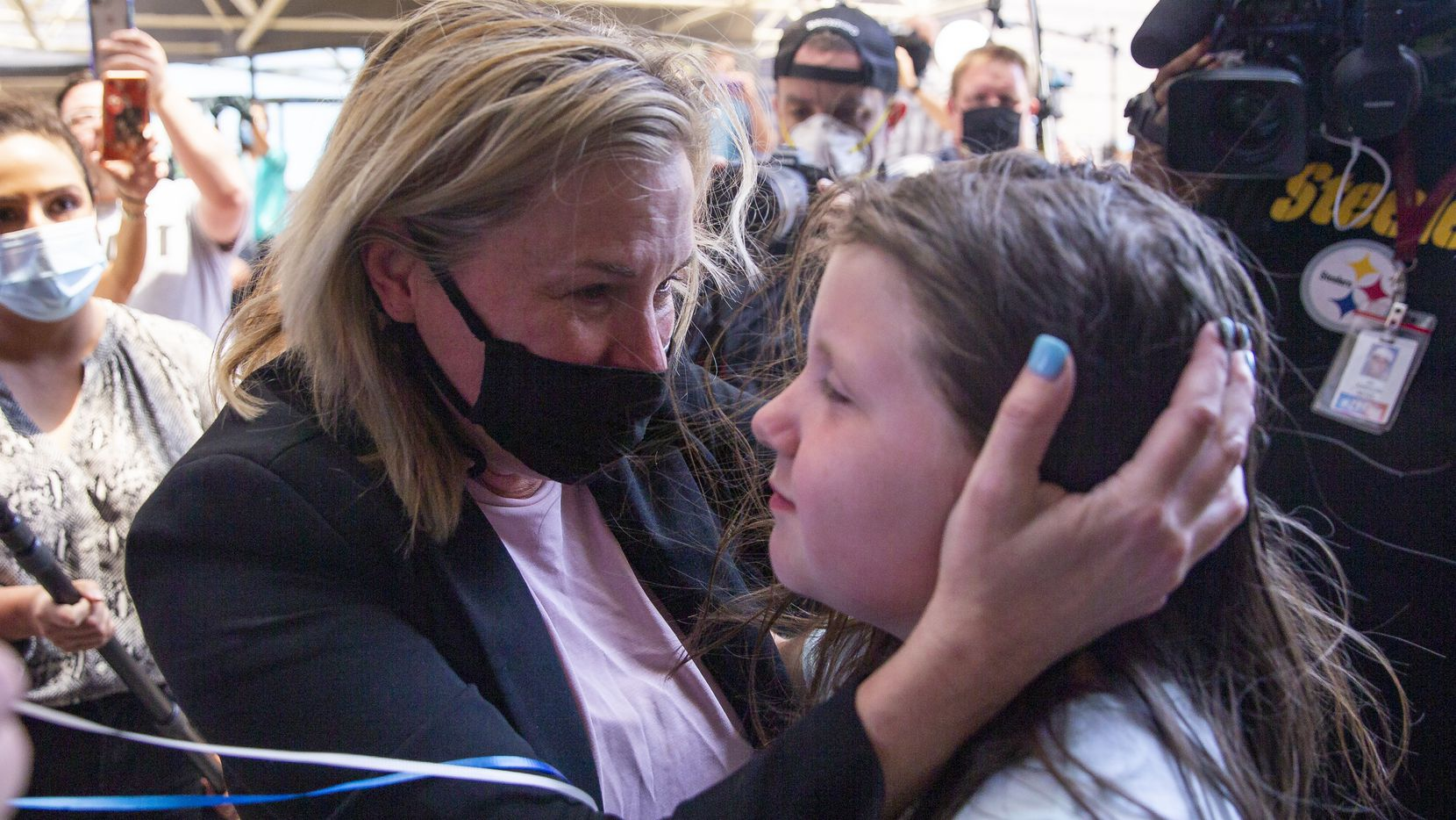 Dallas salon owner Shelley Luther, center, hugs Savannah Holt, 10, of Garland, after Luther was released from the Dallas County Jail on Thursday. The Texas Supreme Court ordered Luther be freed.