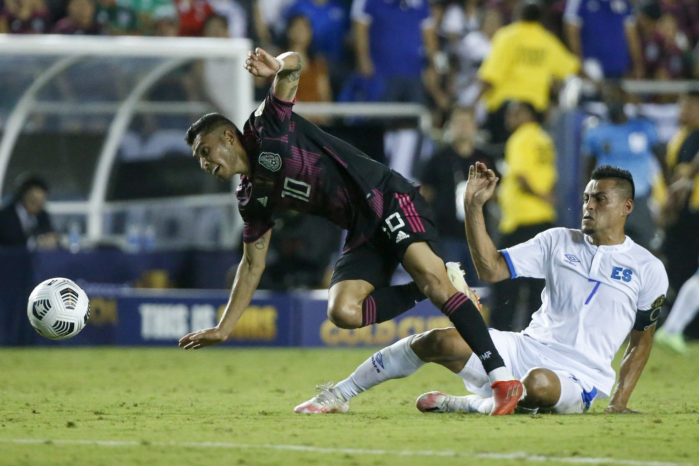 El Salvador midfielder Darwin Cerén (7) tackles Mexico midfielder Orbelín Pineda (10) during the second half of a CONCACAF Gold Cup Group A soccer match at the Cotton Bowl on Sunday, July 18, 2021, in Dallas. (Elias Valverde II/The Dallas Morning News)