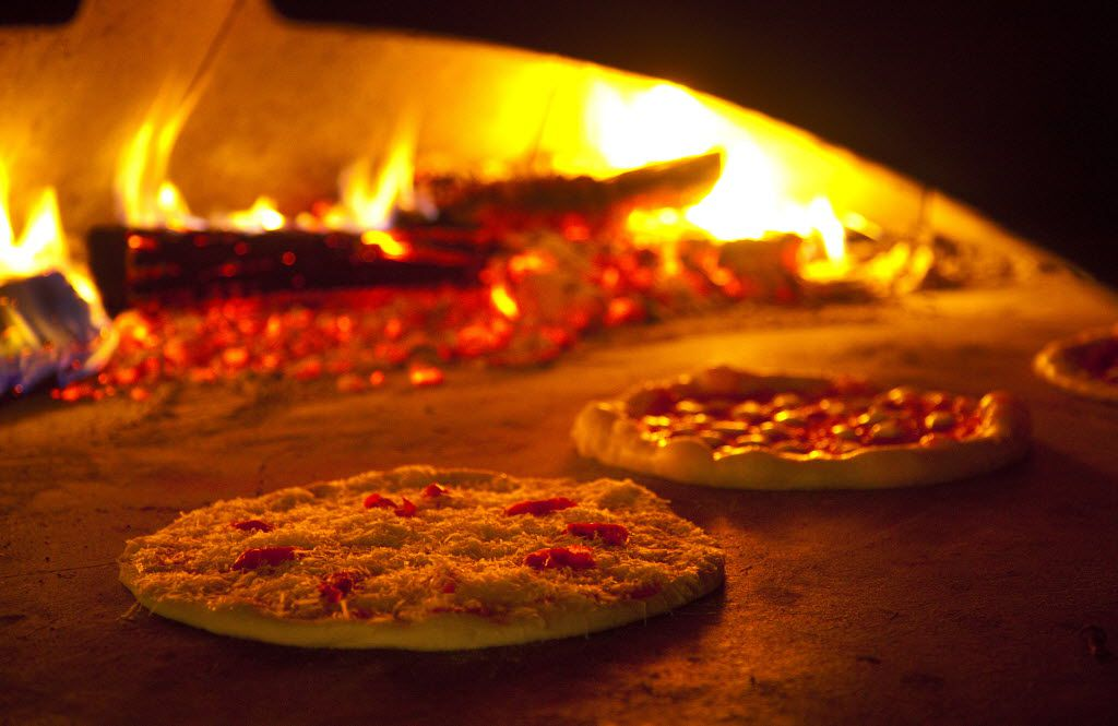 A freshly prepared  Burrata Mozzarella Pie is sild into the wood fired oven at Fireside Pies