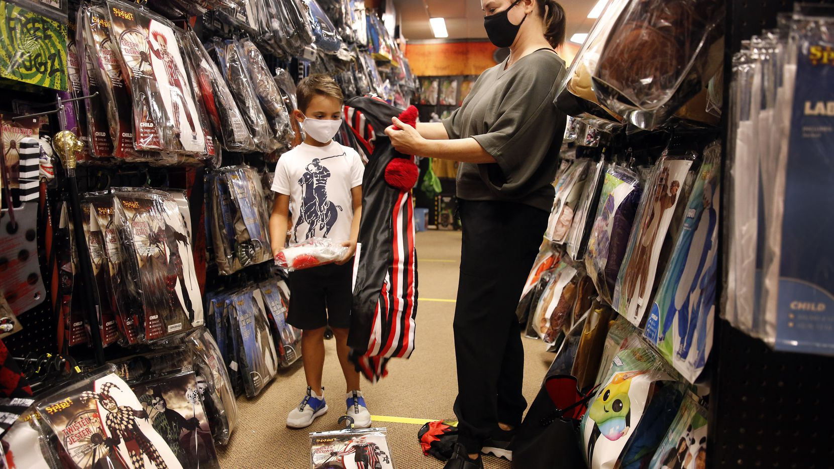 Carey Marin of Richardson sees if a twisted circus clown outfit will fit her son, Joshua, at Spirit Halloween, a pop-up store on Coit Road in Dallas, Thursday, October 1, 2020.