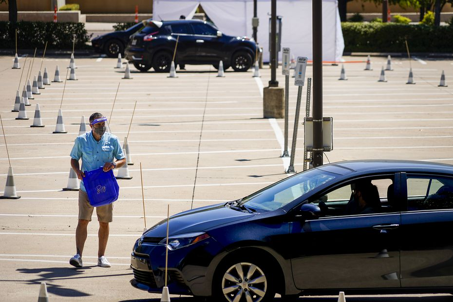 Jason Cotton, vice president of hospitality for the Labora Group, delivers a bag of food to a motorist as Dr. Pedro Salcido (background), of Urgent HomeMD, conducts a COVID-19 drive-thru test in a downtown parking lot on Tuesday, Aug. 18, 2020, in Dallas.