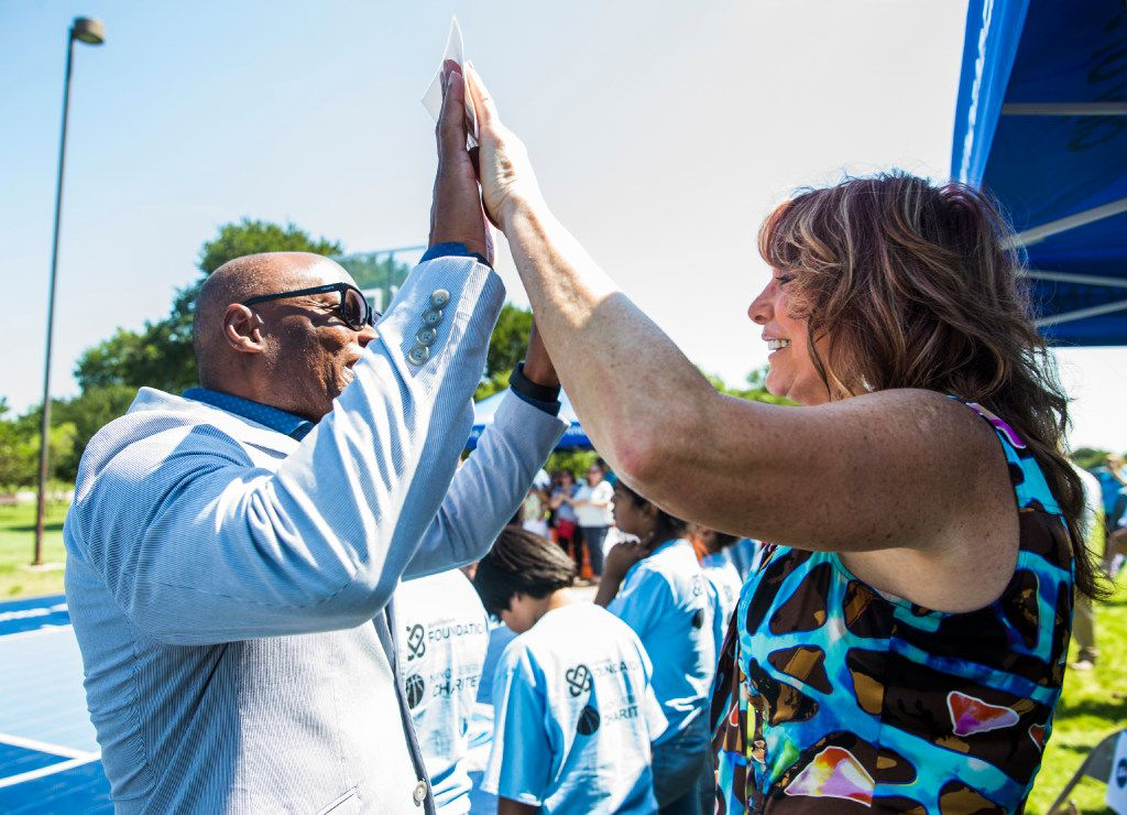Former Dallas Police Chief David Brown high-fives Nancy Lieberman at the Dream Courts opening Friday.