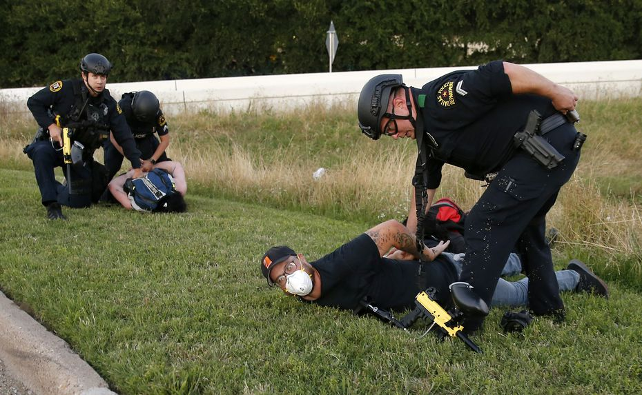 Photographer Chris Rusanowsky (right) is arrested just minutes after capturing the pepper ball shooting up close.