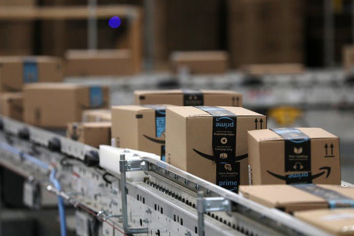 Packages pass down a conveyor belt before receiving a shipping label at Amazon in Shakopee, Minn.