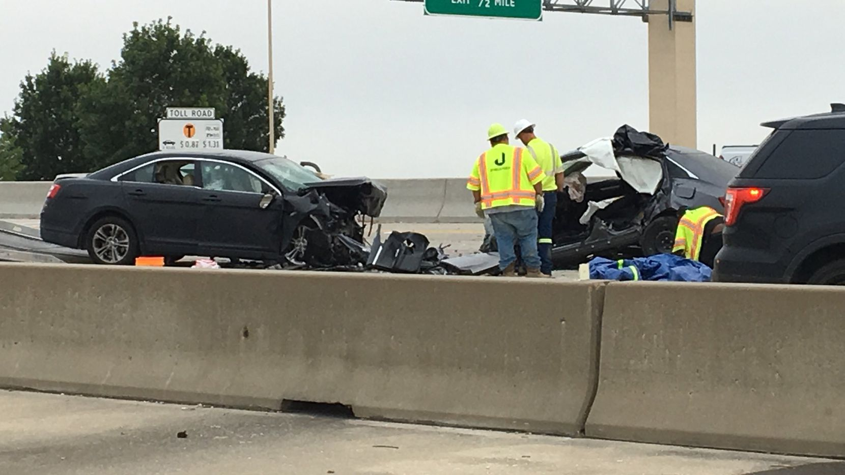 Crews prepare to move two cars off the Bush Turnpike near Richardson and Garland on Thursday morning. Both drivers were killed in a wrong-way crash.
