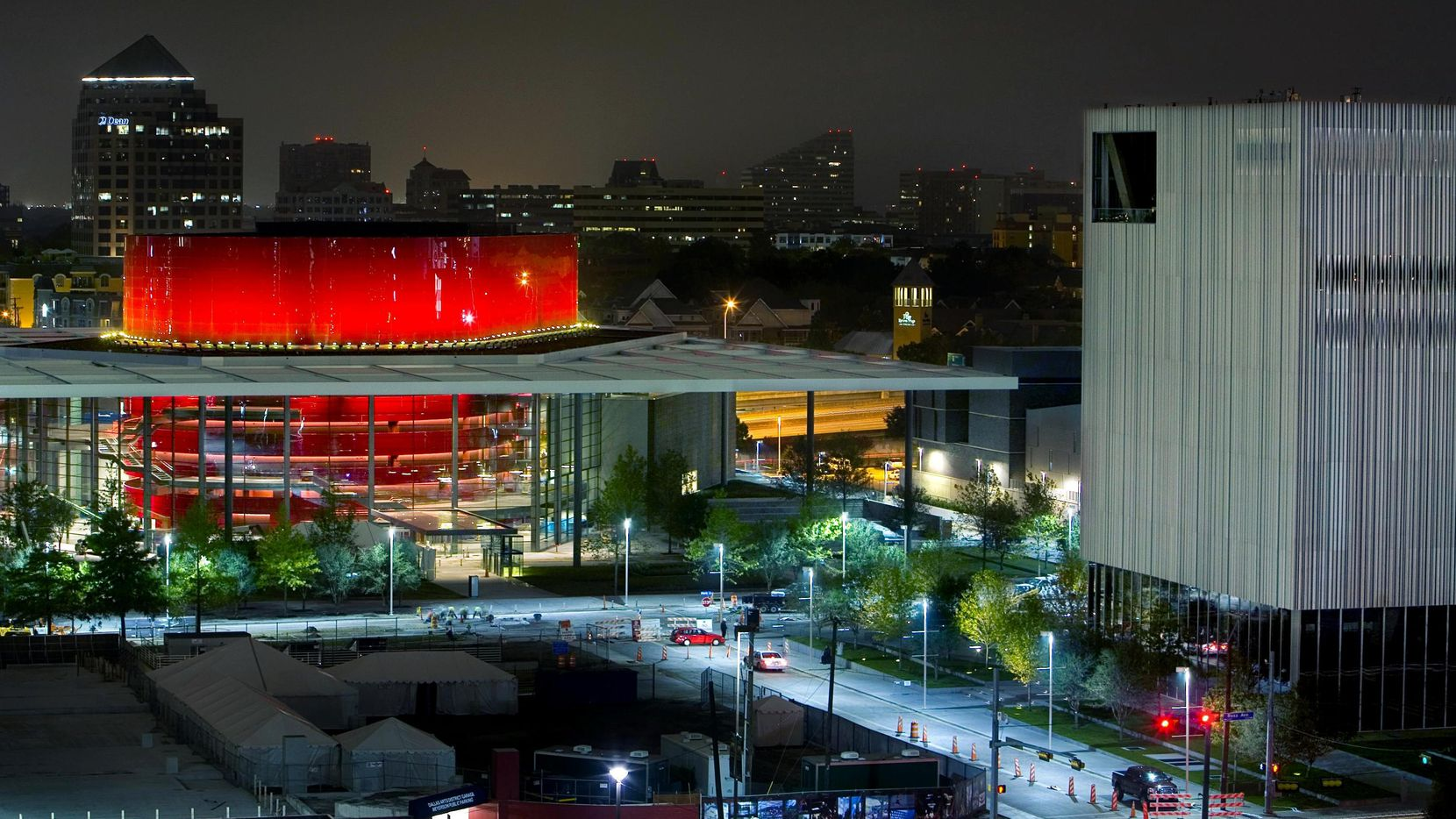 The red drum of the Margot and Bill Winspear Opera House glows in the night, with the Dee and Charles Wyly Theatre to the right.
