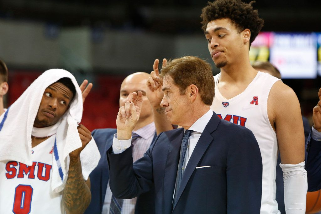 SMU head coach Tim Jankovich shares a glance with guard Jamal McMurray (0) as forward Ethan Chargois (25)  towers over the two during the playing of the school song following the Mustang's 77-57 victory over Tulsa.  The two teams played their NCAA mens basketball game at SMU's Moody Coliseum in Dallas on January 12, 2019. (Steve Hamm/ Special Contributor)