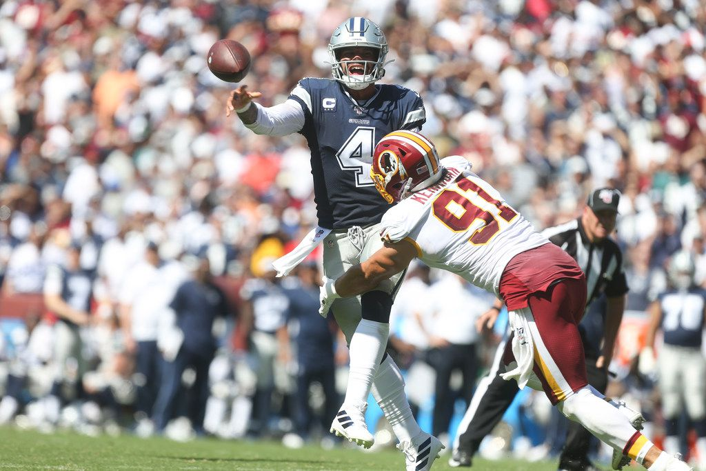 Dallas Cowboys quarterback Dak Prescott (4) makes a pass under pressure from Washington Redskins outside linebacker Ryan Kerrigan (91) during the first half of an NFL game at FedEx Field in Landover, Maryland on Sunday, September 15, 2019.