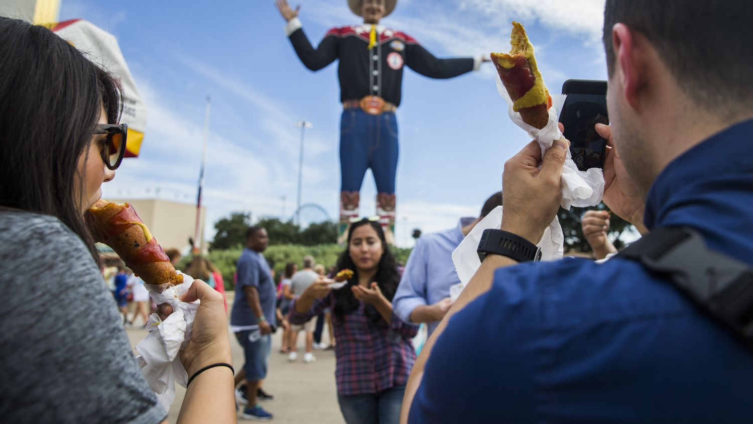 Fairgoers eat Fletcher's Corny Dogs while taking photos of Big Tex on Wednesday, October 4, 2017 at the State Fair of Texas in Dallas.