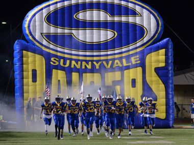 The Sunnyvale football team runs onto the field.
