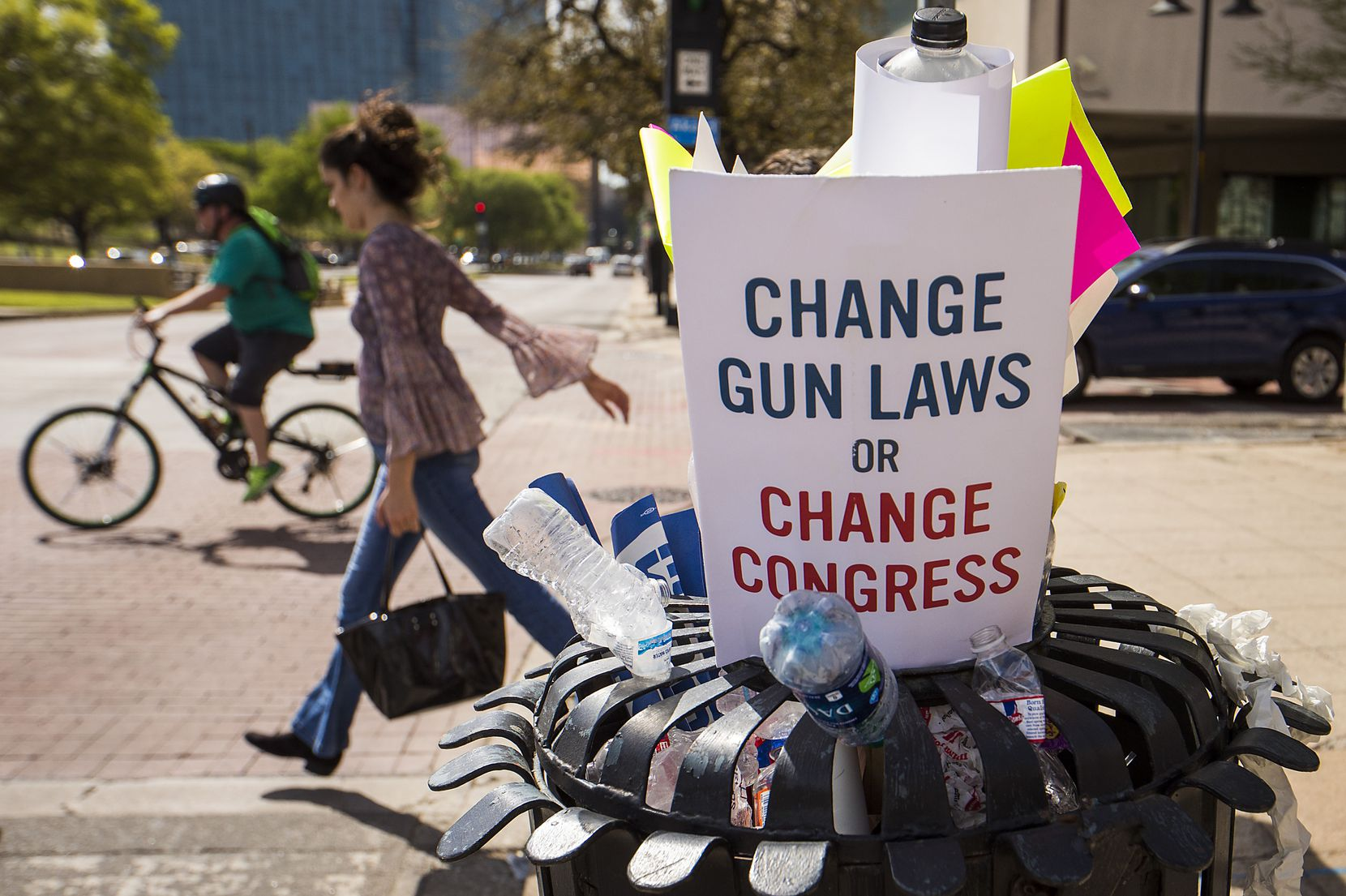 Protest signs and water bottles fill a sidewalk trash bin after a rally and march in support of gun safety laws.
