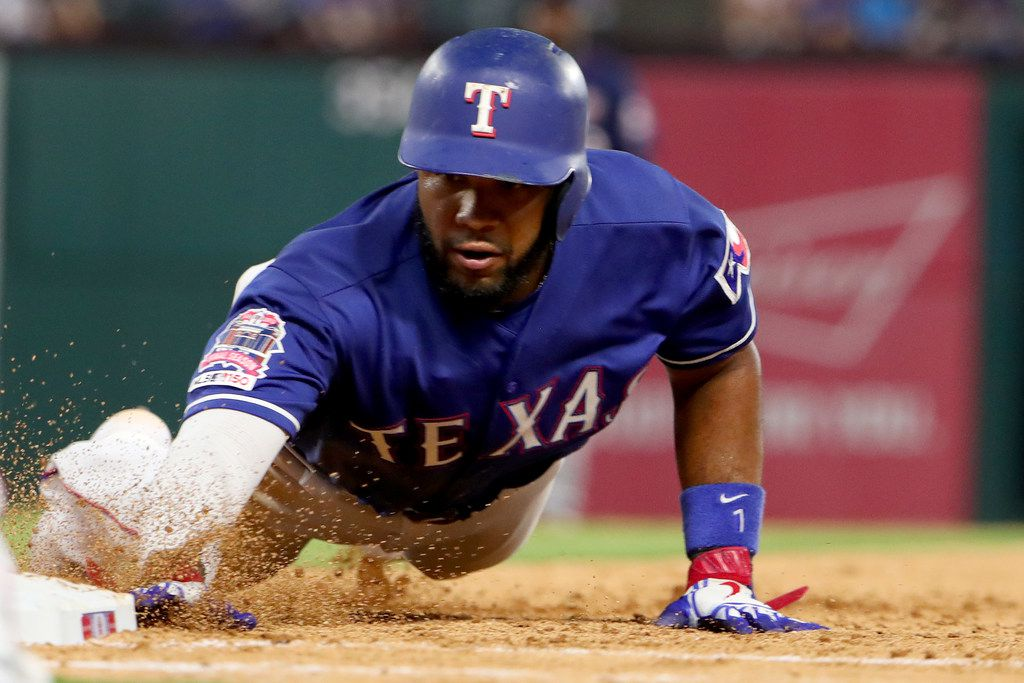 ARLINGTON, TEXAS - AUGUST 16: Elvis Andrus #1 of the Texas Rangers dives back to first base safe against the Minnesota Twins in the bottom of the fourth inning at Globe Life Park in Arlington on August 16, 2019 in Arlington, Texas. (Photo by Tom Pennington/Getty Images)
