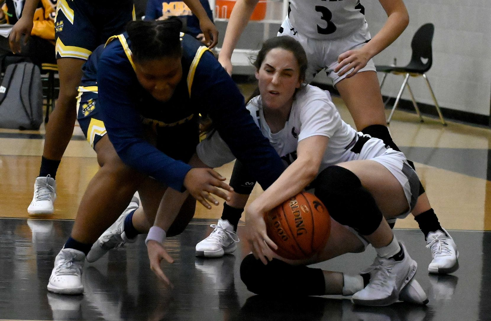 McKinney's Karlan Moore, left, Denton Guyer's Evie Goetz go after a loose ball in the second half of a girls high school basketball game between McKinney and Denton Guyer, Tuesday, Dec. 15, 2020, in Denton, Texas.