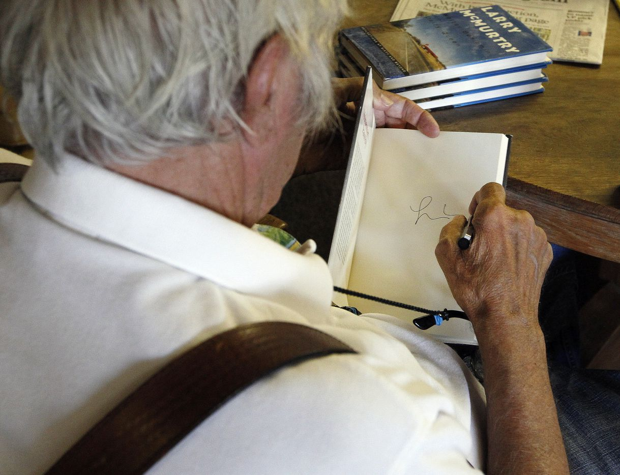 Larry McMurtry signs books for customers after his auction from his private collection in downtown Archer City in 2012.