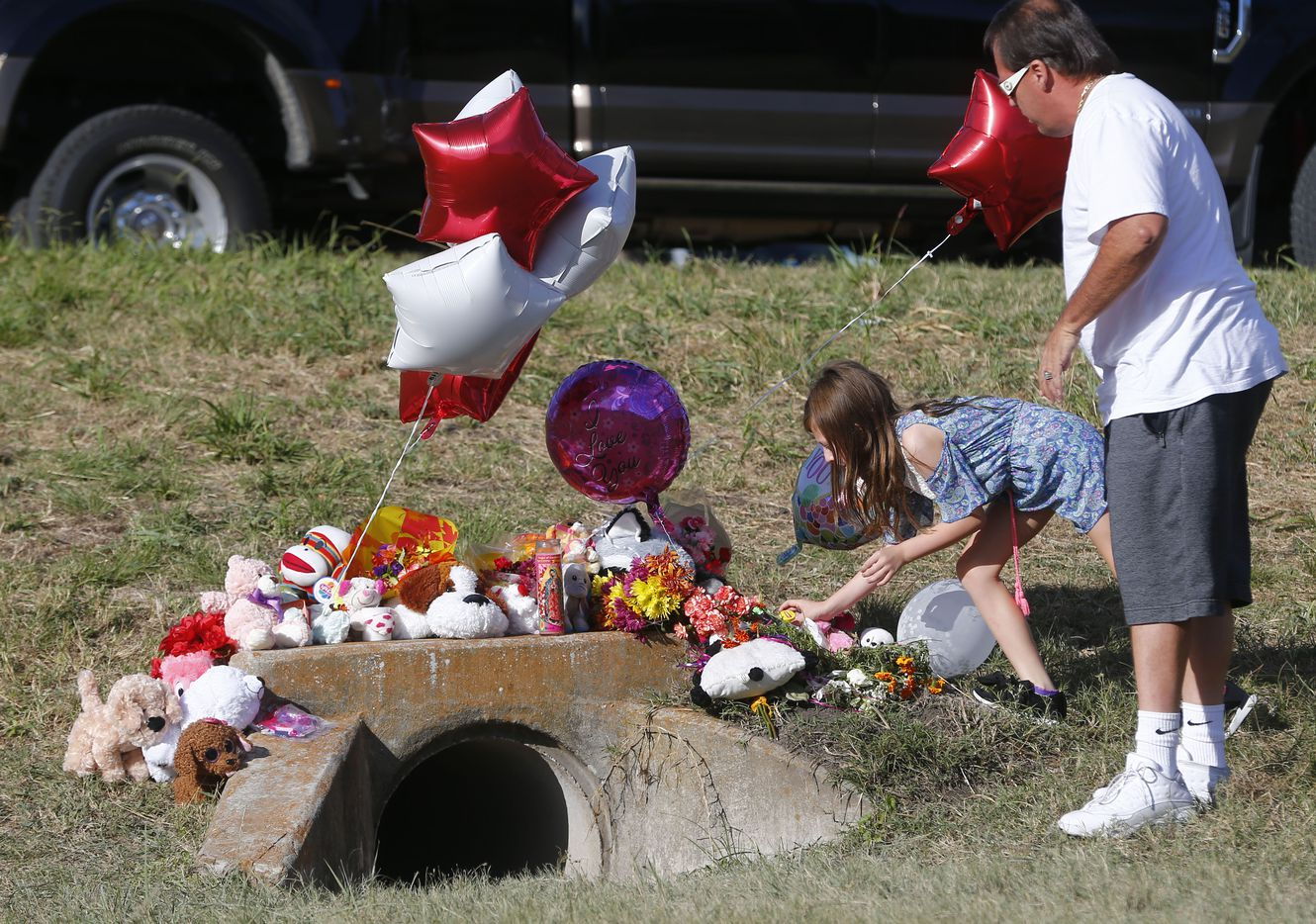 Miley Grahmann, 8, leaves a bear with a jar of Carmex (in case her lips get chapped in Heaven) with her father Patrick Grahmnann in the area where the body of a small child was found Sunday morning during the search for a missing 3-year-old girl, Richardson police announced Sunday. Police have not yet confirmed that the body is that of Sherin Mathews, who has been missing since Oct. 7. Photo taken on Oct. 23, 2017 in Richardson, Texas. Miley had seen Sherin Mathews when riding around with her father. (Nathan Hunsinger/The Dallas Morning News)