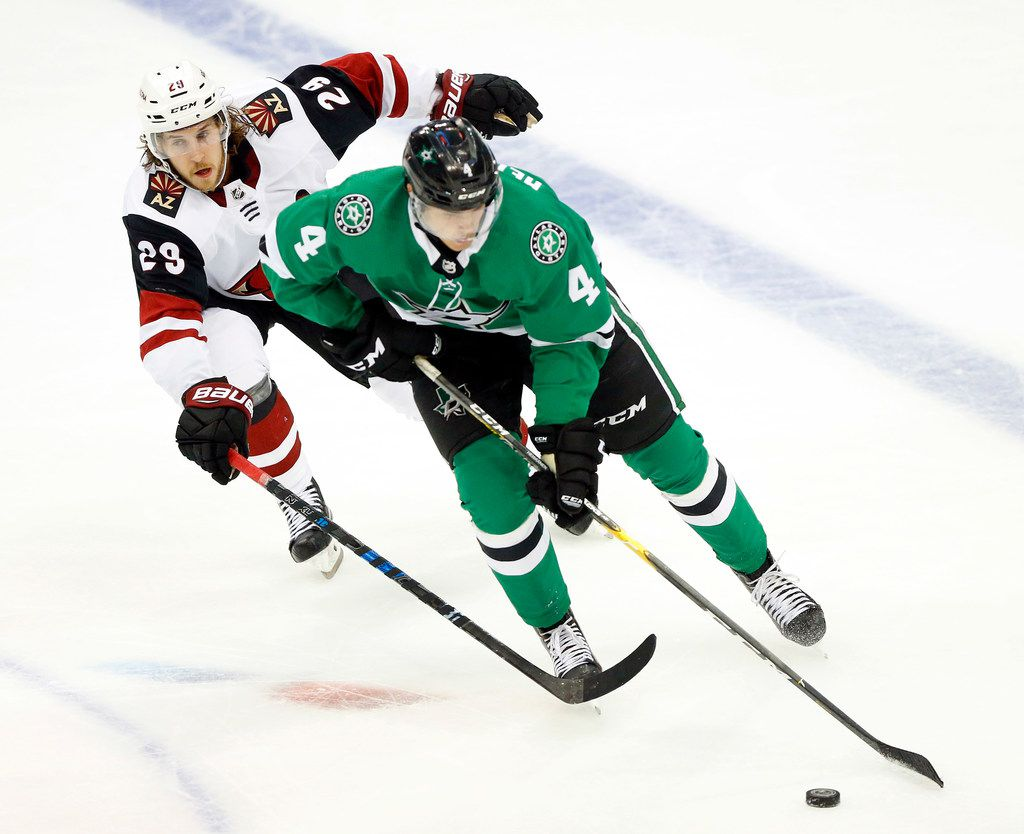 Dallas Stars defenseman Miro Heiskanen (4) keeps the puck away from Arizona Coyotes right wing Mario Kempe (29) as they skate up the ice in the third period of their season-opening game at the American Airlines Center in Dallas, Thursday, October 4, 2018. (Tom Fox/The Dallas Morning News)
