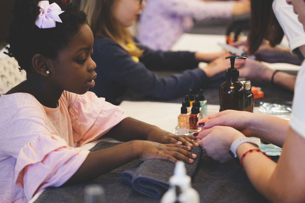 A young girl gets her nails painted by a technician at Verbena Parlor and Social House in Uptown.