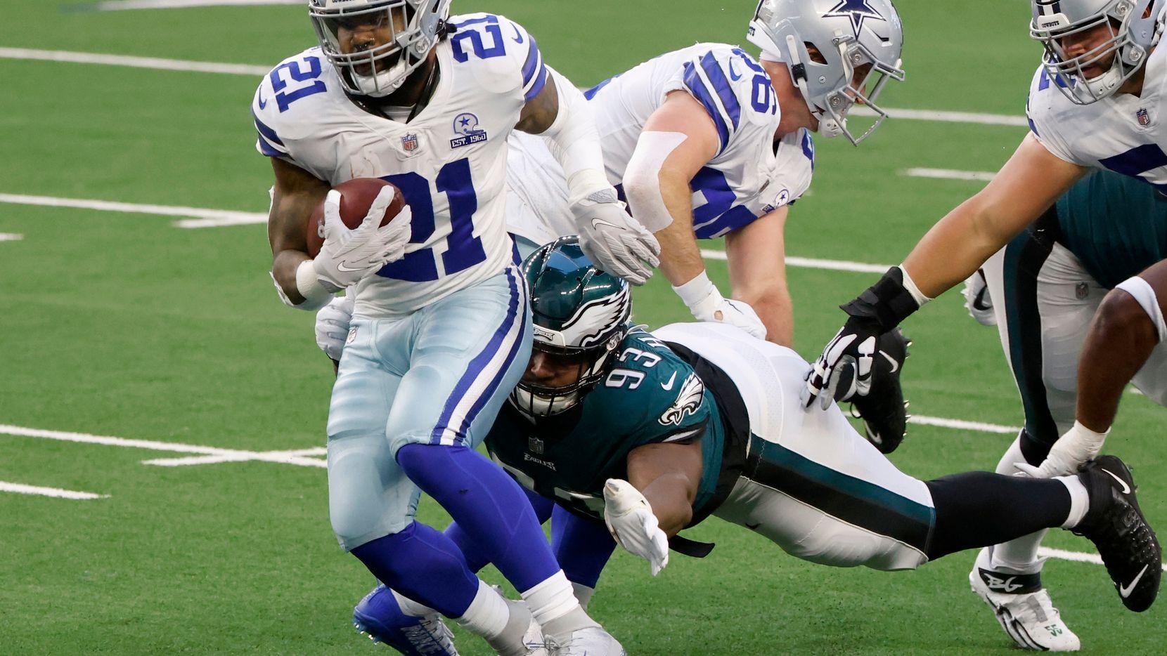 El corredor de los Cowboys de Dallas, Ezekiel Elliott (21), rompe una tacleada ante los Eagles de Filadelfia en el juego del 27 de diciembre de 2020 efectuado en el AT&T Stadium de Arlington.