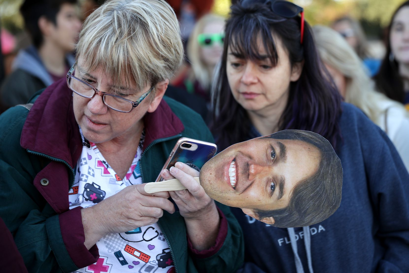 Beto O'Rourke supporters follow a live video live feed to keep track of his scheduled arrival at a Nov. 2 campaign rally at Wayne Frady Park in Lewisville.