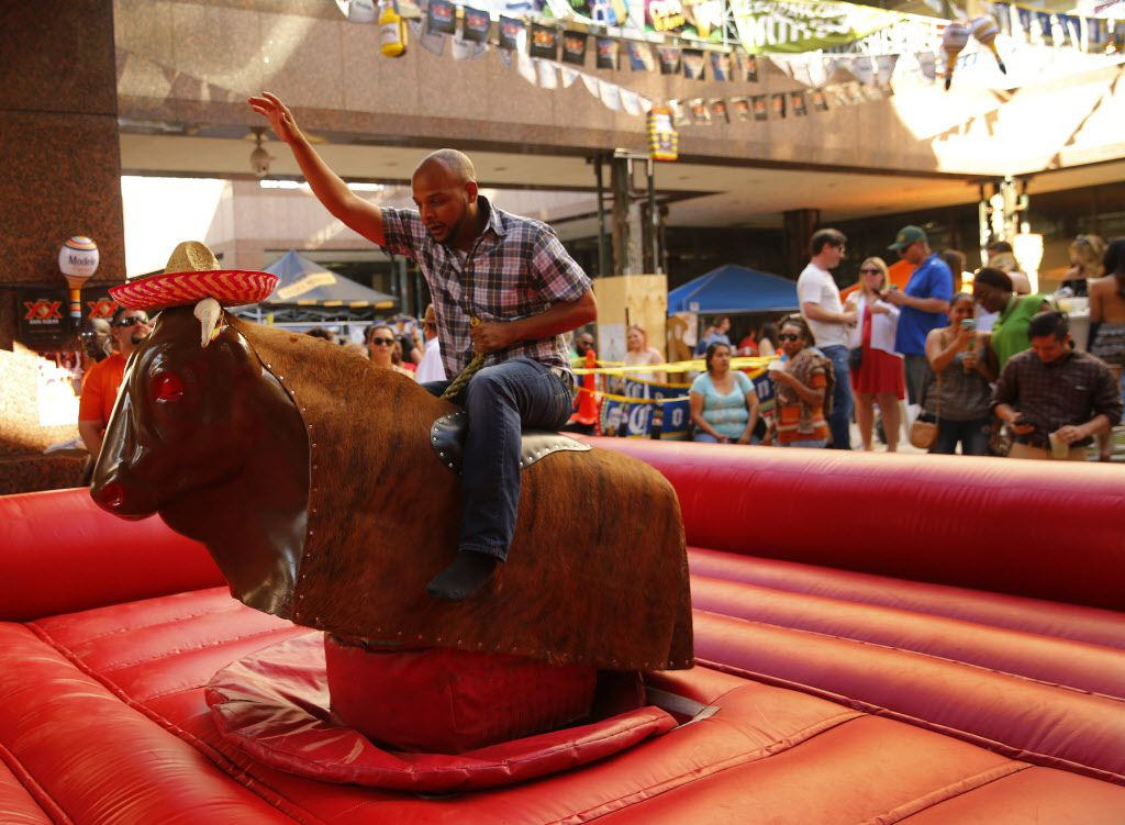 Cameron Rockwall of Dallas rides a mechanical bull during a Cinco De Mayo celebration at Mattito's Tex-Mex restaurant in the Uptown area of Dallas, Thursday, May 5, 2016.  (Tom Fox/The Dallas Morning News)