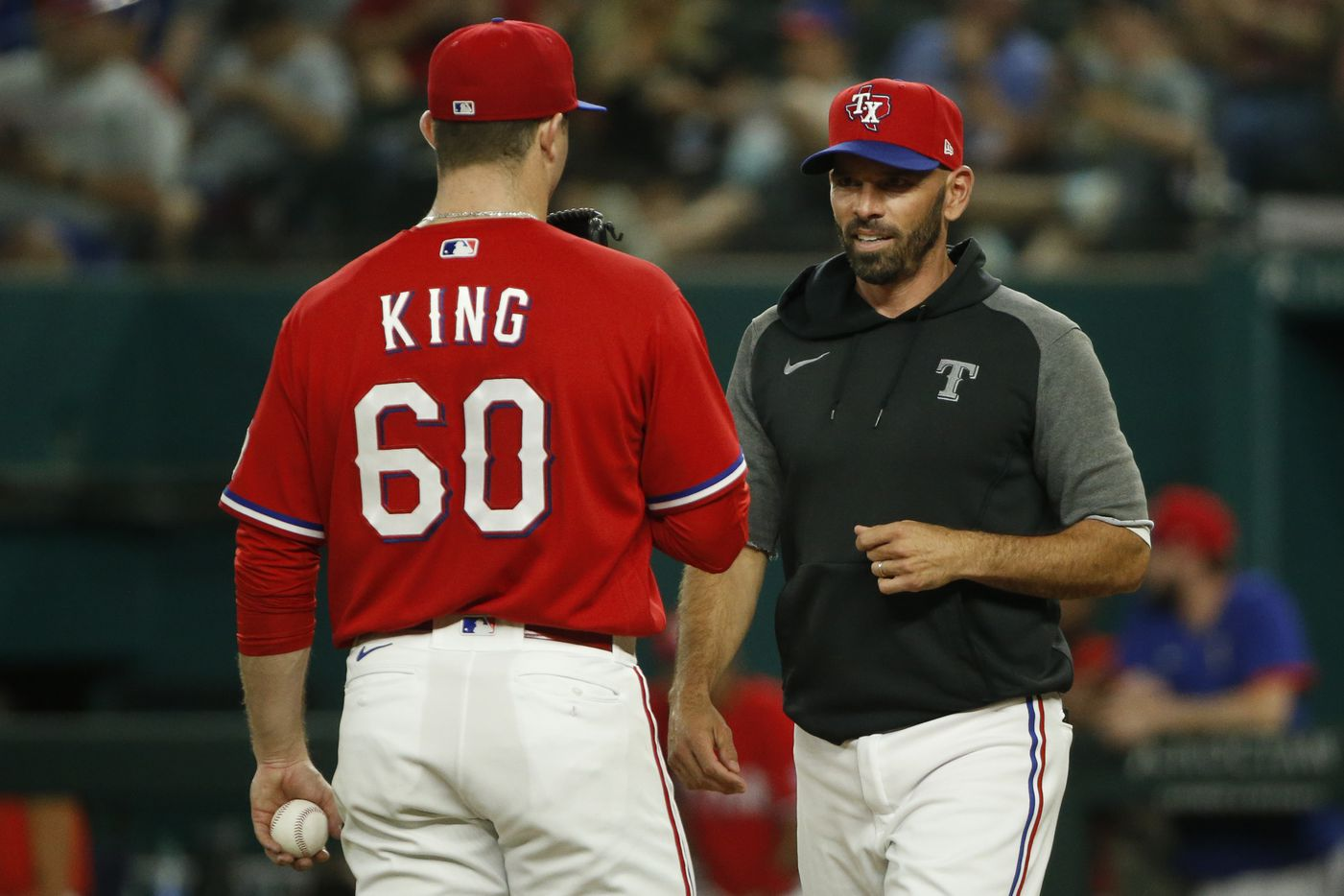 Texas Rangers relief pitcher John King (60) talks with Texas Rangers manager Chris Woodward (8) during a mound visit in the ninth inning against the Kansas City Royals at Globe Life Field on Friday, June 25, 2021, in Arlington. (Elias Valverde II/The Dallas Morning News)