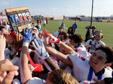 Parish Episcopal's football team hoists the trophy after receiving it during the awards presentation after defeating Plano John Paul II 42-14 in the TAPPS Division I State Championship game at Waco Midway's Panther Stadium in Hewitt, Texas on Friday, December 6, 2019.