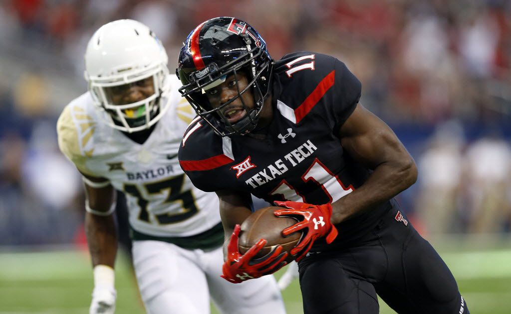 Texas Tech Red Raiders wide receiver Jakeem Grant (11) pulls in a second quarter touchdown catch ahead of Baylor Bears safety Terrell Burt (13) at AT&T Stadium in Arlington, Texas, Saturday, November 29, 2014.