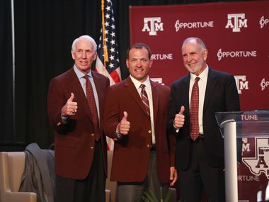 Texas A&M's interim Athletic Director R.C. Slocum poses alongside new Athletic Director Ross Bjork and University President Michael K. Young.