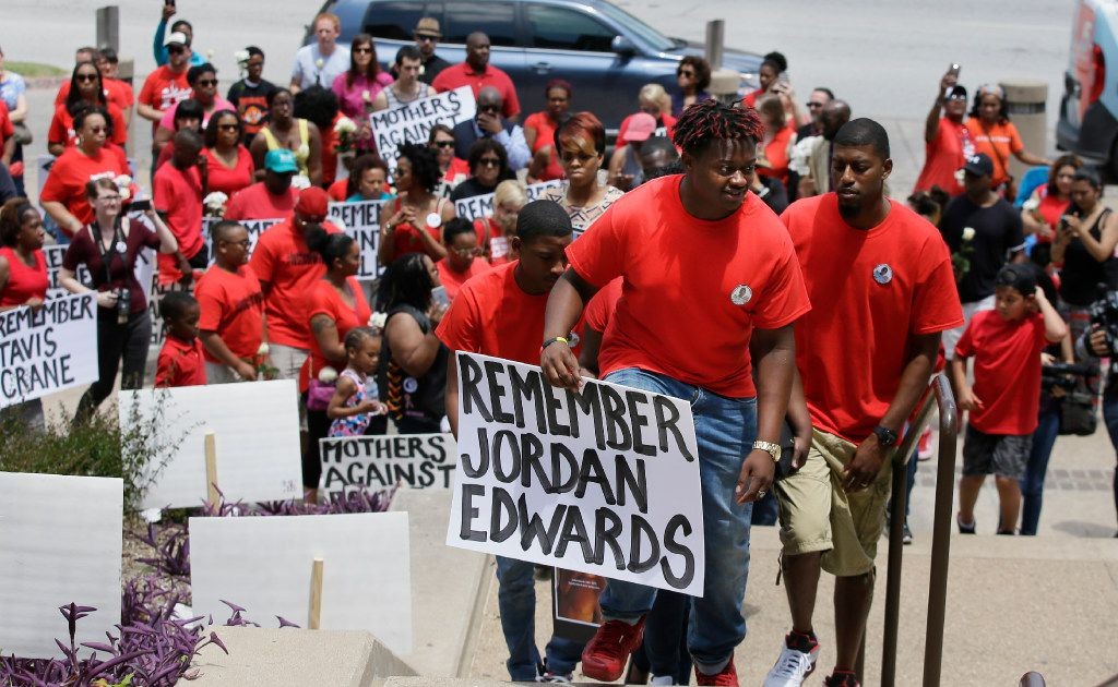 Slain teen Jordan Edwards' brother Vidal Allen (front) led his family up the courthouse steps during a protest in Dallas in May. Balch Springs officer Roy Oliver was fired and charged with murder after fatally shooting Jordan, a teenage passenger in a car trying to leave a house. A growing number of law enforcement agencies, including the U.S. Department of Justice, either deeply discourage or prohibit shooting at a moving car unless someone inside is shooting back.