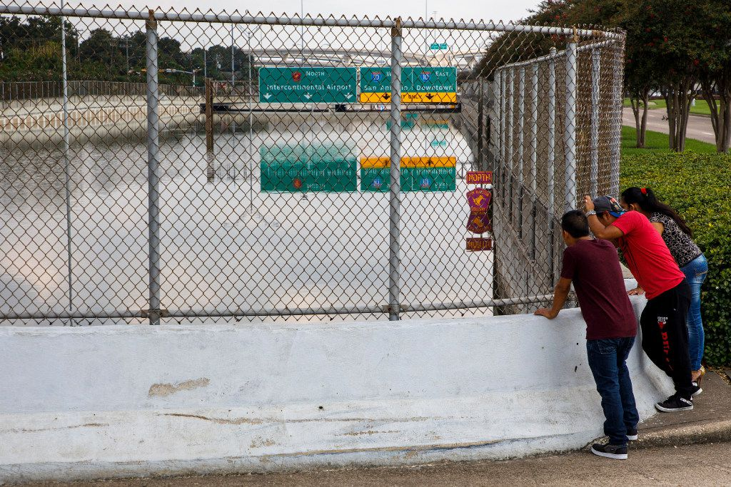 Onlookers gather on a bridge on Memorial Drive to see the nearly 16 feet of Hurricane Harvey flood water still fills Beltway 8, the Sam Houston Tollway, on Monday in Houston. (Smiley N. Pool/The Dallas Morning News)