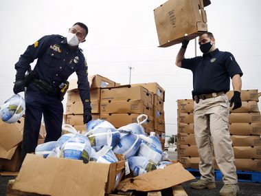 Dallas Police Department UNIDOS outreach team members Sgt. Eddie Reyes (right) and Lt. Stephen Williams unload frozen turkeys for volunteers from First Untied Bank, Hunger Busters and Canales Furniture during a Thanksgiving turkey handout in the Pleasant Grove area of Dallas, Saturday, November 21, 2020. The group has been working to build trust between the Latino community and police the past five years. (Tom Fox/The Dallas Morning News)