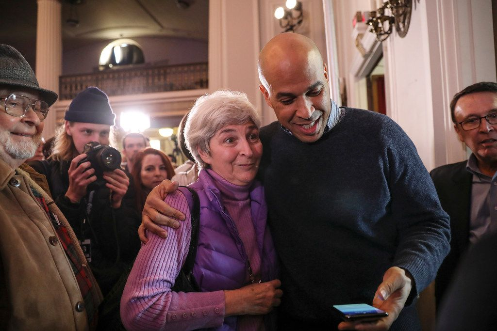 Sen. Cory Booker, D-N.J., prepares to take a selfie with a supporter at a post-midterm election victory celebration in Manchester, N.H., on Dec. 8, 2018.