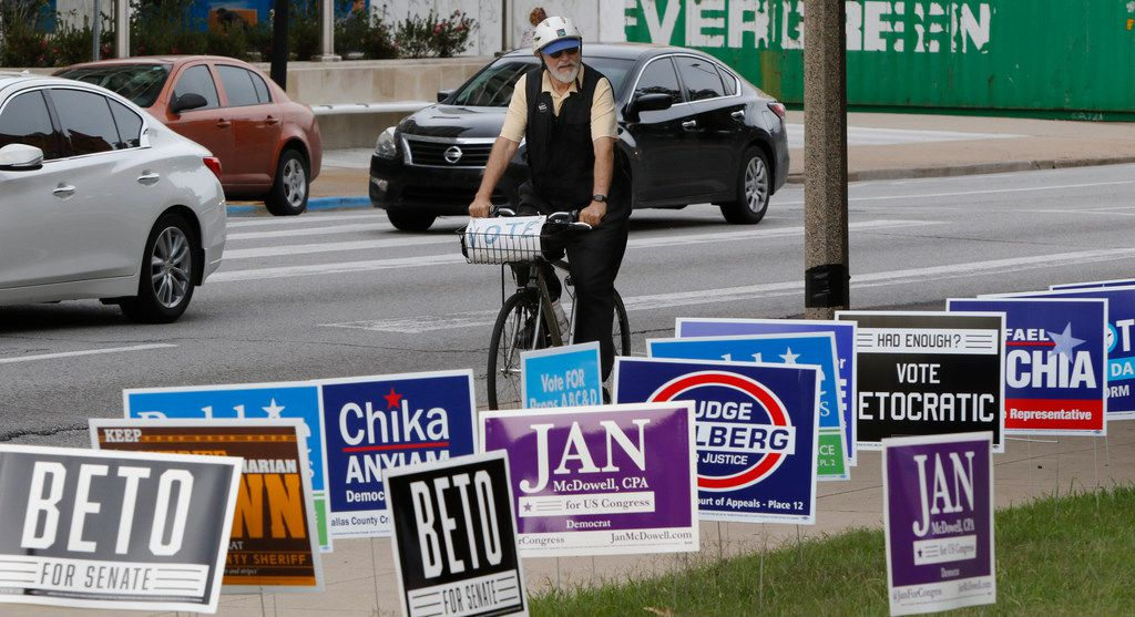 Gene Lantz rides past candidates' signs near the George L. Allen, Sr. Courts Building in Dallas at 600 Commerce St on Oct. 22, 2018, on his way to a voting rally on the opening day of early voting across the State of Texas. Early voting starts Oct. 22 and ends Nov. 2.